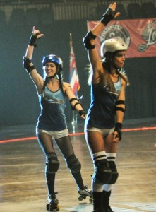 Actresses Michelle Borth (left) and Tiffany Dupont acknowledge fans in roller derby scene.